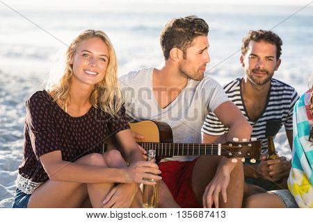 Friends drinking beer and playing guitar on a sunny day