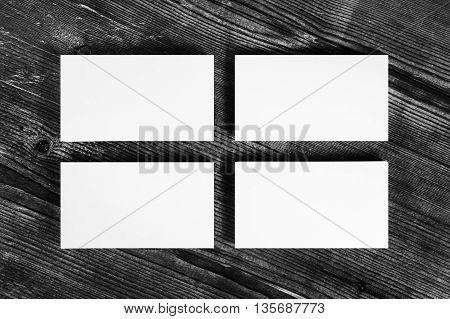 Photo of blank white business cards on wood table background.. Mock-up for branding identity for designers. Isolated with clipping path. Top view.