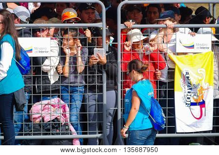 QUITO, ECUADOR - JULY 7, 2015: People waitting to see pope Francisco in Ecuador, mass with thousand people. Metalic mesh to protect the pope and volunteers.