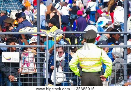 QUITO, ECUADOR - JULY 7, 2015: Police guarding the seciruty of people at pope Francisco mass, posters and people behind a metalic mesh.