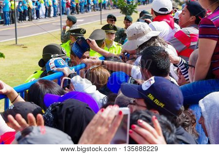QUITO, ECUADOR - JULY 7, 2015: People very near from the metal fence, police guarding visitors on pope Francisco mass.