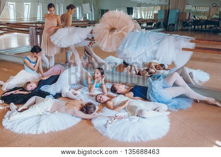 Thr seven ballerinas lying on tatus on floor in the rehearsal hall of the theater