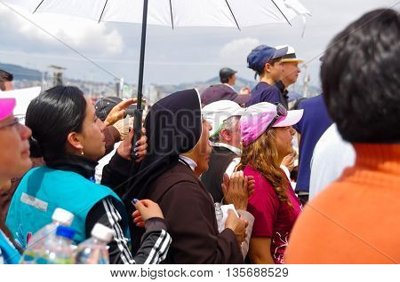 QUITO, ECUADOR - JULY 7, 2015: In the middle of thousand people a nun is praying under the sun, a police is behind her.