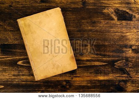 Old vintage book on rustic wooden table blank covers as copy space top view