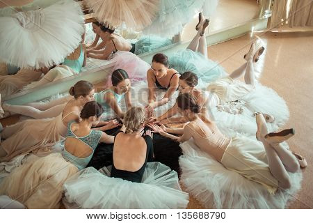 The seven ballerinas lying on floor in the rehearsal hall of the theater