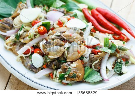 spicy cockle salad on wooden background selection focus