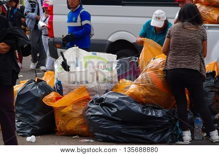 QUITO, ECUADOR - JULY 7, 2015: After pope Francisco mass, garbage cleaners putting all the trash in bags.