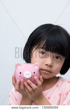 Asian Child With Piggy Bank