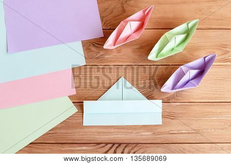 Set of colored ships on wooden background. How to fold paper ship. Origami folding instruction. Learn to make origami paper items. Art project idea for kindergarten and summer camps