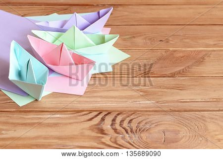 Colorful ships paper folding, sheets of colored paper on a wooden table with empty space for text. Paper art crafts for children. Origami for kids. Children summer background