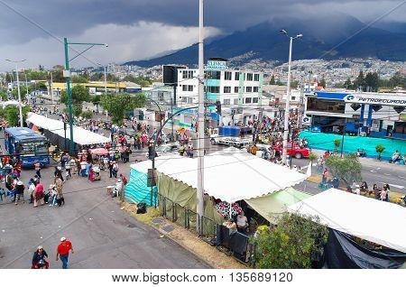 QUITO, ECUADOR - JULY 7, 2015: People walking around pope mass event, cars and buses arriving to the place.