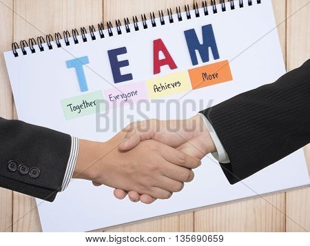 Handshake of two business mans waring black suit on word spell TEAM on white notebook (Teamwork concept)