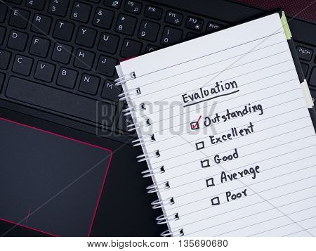 Handwriting performance evaluation on white notebook on laptop keyboard