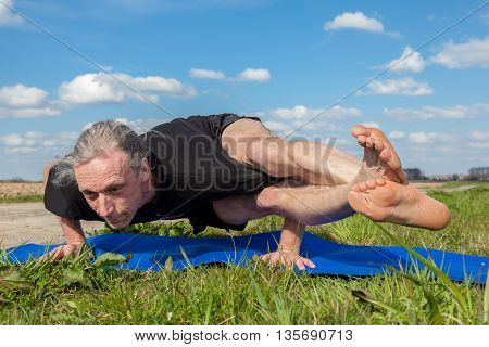 on an sunny day this man enjoys astavakrasana yoga in nature