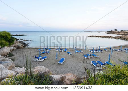 PROTARAS CYPRUS - JUNE 12 2016: Photo of beach and sea in protaras cyprus island with beach chairs and rocks at sunset on bank holidays.