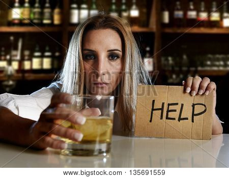 drunk alcoholic blond woman drinking whiskey glass asking for help holding message board depressed wasted and sad at bar or pub in alcohol abuse and housewife alcoholism