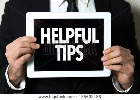 Business man holding tablet with the text: Helpful Tips
