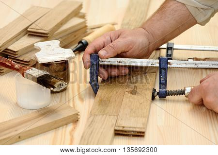 Carpenter hands working with wooden planks closeup