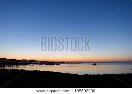 Photo of beach and sea in protaras cyprus island with hotels and a boat silhouettes at sunset.
