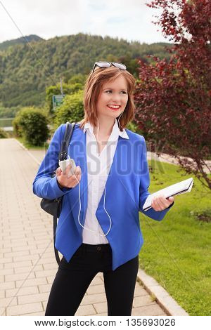 Fashionable dressed woman with cell phone and taking notes on the phone standing in a park