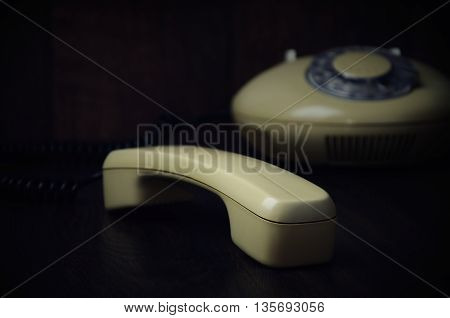 Old-fashioned Handset And Phone On A Dark Wooden Background. Horizontal, Toned Image