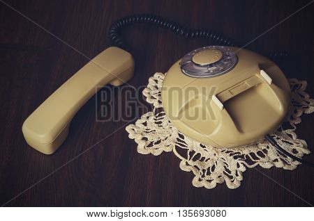 Toned Image Of An Old-fashioned Phone On Knitted Napkin On A Dark Wooden Table. Top View, Horizontal
