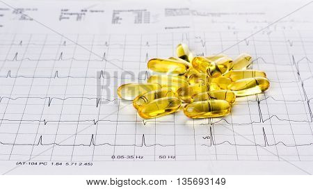 Omega 3 gel capsules on an ecg test result paper background