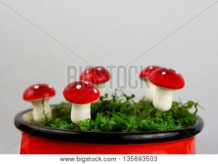 Fairytale background with agaric and moss in a red enameled cup