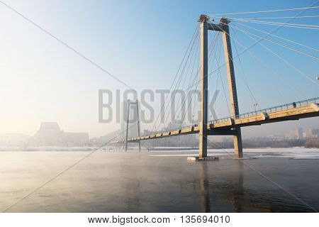 View of the bridge through the river in foggy frosty day.