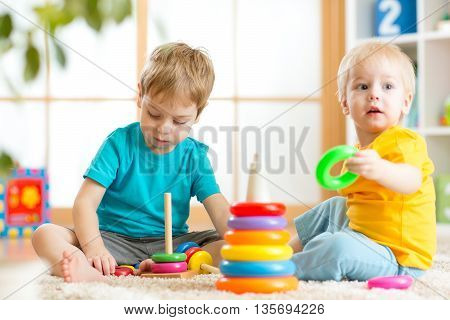 Toddlers kids playing with wooden blocks on floor at home