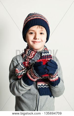 Winter Child Boy drink Tea or Coffee. Winter Clothes. Sweater Hat and Scarf