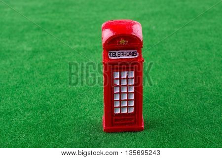 Red color Phone booth on green grass