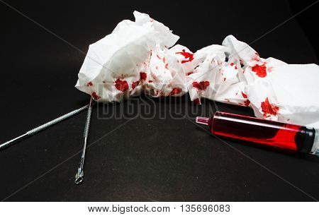 Paper bloody syringes and instruments in a black background.