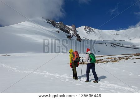 Male and female climbers ascend on a snowy volcano. Turkey