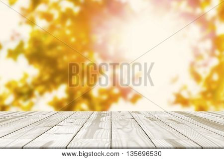 Wood Table Top On Maple Leaves Blurred In Background With Sunlight