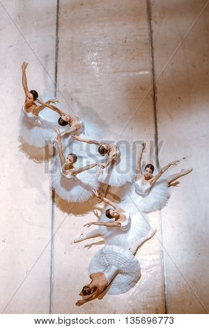 The top view of ballerinas on floor in the rehearsal hall of the theater