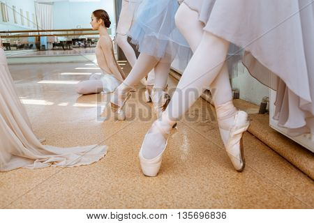 The close-up feet of young ballerinas in pointe shoes against the floor