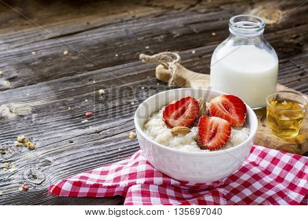 Healthy homemade breakfast. Fresh milk porridge with garden ripe strawberries in white ceramic bowl on a simple wooden dark background with a bottle of honey and cream. selective focus