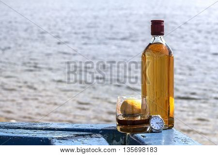 Bottle of whiskey and tumbler with a watch on shore of lake