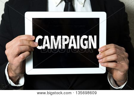 Business man holding tablet with the text: Campaign