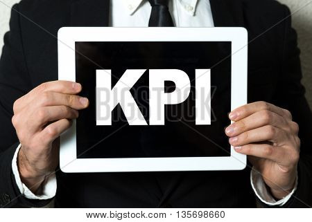 Business man holding tablet with the text: KPI
