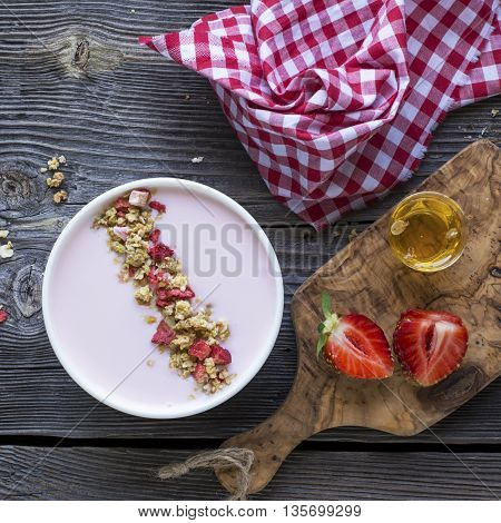 Yogurt smoothies Bowl. Healthy breakfast. Natural bowl of strawberry yogurt with strawberry granola with dried strawberries on a simple wooden background.