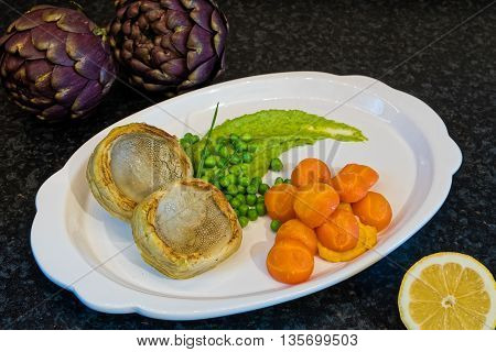 Plate of cooked artichokes, served with peas and carrots
