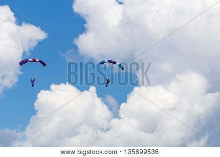 two parachutist descends to earth in the clouds and blue sky view from the ground