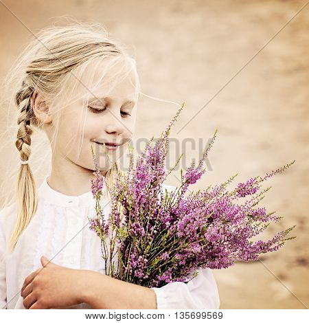 Young Girl Outdoors. Happy Girl with Heather Flowers in Great Britain Heath