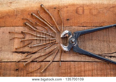 Pincers with rusted nails on timber background. DIY