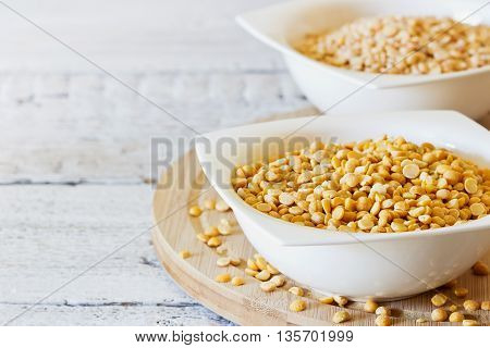 Dry peas in a ceramic bowl on a white wooden table. Bio healthy food. Selective focus. Copy space for you text