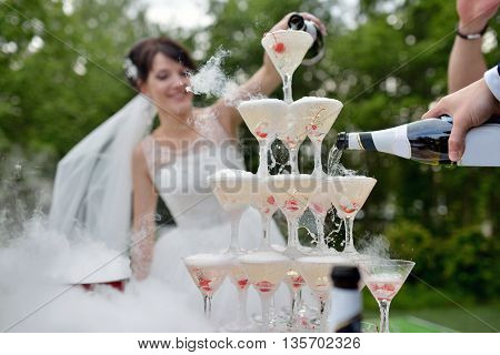 Beautiful Wedding Couple Is Pouring Champagne Indoors. Colorful Glasses For Alcohol With Berries For