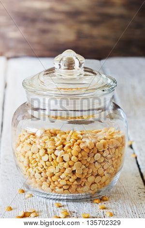 Dry peas in a glass jar on a white wooden table. Bio healthy and diet food. Selective focus