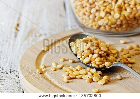 Dry peas in a spoon on a cutting board on a white wooden table. Close-up. Bio healthy and diet food. Selective focus